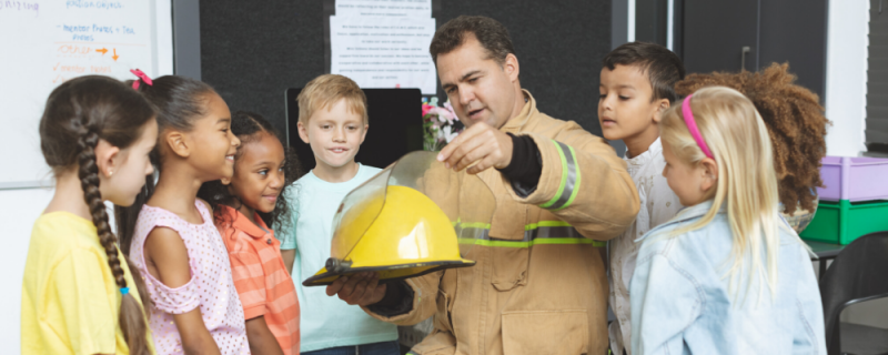fireman showing children how their helmets are built